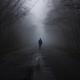 Man in a fog walks down the road