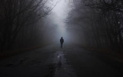 Man in a fog walks down the ro...
